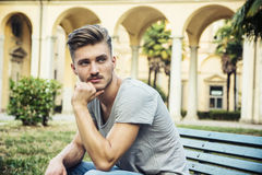 Hübscher blonder junger Mann, der auf Parkbank sitzt Stockfotografie