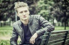 Hübscher blonder junger Mann, der auf Parkbank sitzt Stockfotos