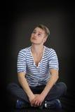 Hübscher blonder junger Mann, der auf schwarzem Hintergrund sitzt Stockfoto