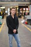 Hübscher blonder junger Mann, der in der Station oder im Einkaufszentrum steht Stockbild