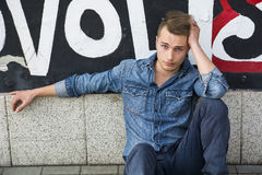 Hübscher blonder junger Mann, der gegen bunte Graffitiwand sitzt Stockfoto