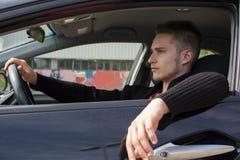 Hübscher blonder junger Mann, der in seinem Auto sitzt Lizenzfreie Stockfotos