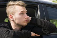 Hübscher blonder junger Mann, der in seinem Auto sitzt Stockfotografie
