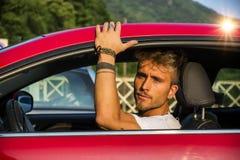 Hübscher blonder junger Mann, der in seinem Auto sitzt Stockfotos