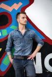 Hübscher blonder junger Mann gegen bunte Graffitiwand Stockbilder