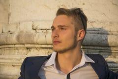 Hübscher blonder junger Mann mit Marmorsäulen hinter ihm Stockbild