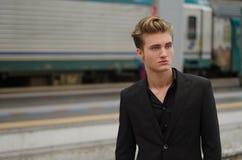 Hübscher blonder junger Mann mit Zug hinter ihm, im Bahnhof Stockfotografie