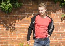 Hübscher blonder junger Mann vor Backsteinmauer Lizenzfreie Stockfotos