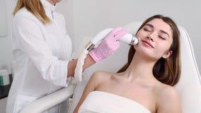 Hübscher blonder Kosmetikerdoktor, der Rf-anhebendes Verfahren für die Frau legt in einen Schönheitssalon tut Hardware Cosmetolog stock video