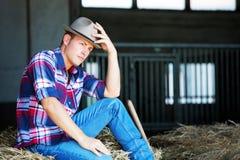 Hübscher blonder Mann in den Jeans, die auf Heuschober sitzen Lizenzfreies Stockfoto