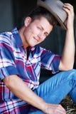 Hübscher blonder Mann in den Jeans, die auf Heuschober sitzen Lizenzfreie Stockbilder