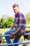Hübscher blonder Mann, der auf Zaun an einem Bauernhof sitzt Stockbild