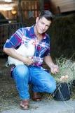 Hübscher blonder Mann, der ein weißes Huhn mit einem Korb von Eiern hält Lizenzfreies Stockfoto