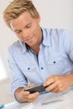 Hübscher blonder Mann, der kurze Mitteilung auf Smartphone sendet Stockfotos
