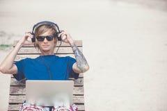 Hübscher blonder Mann, der mit Laptop und Kopfhörern am Strand arbeitet Stockbild