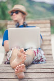 Hübscher blonder Mann, der mit Laptop und Kopfhörern am Strand arbeitet Lizenzfreie Stockfotografie