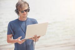 Hübscher blonder Mann, der mit Laptop und Kopfhörern am Strand arbeitet Lizenzfreie Stockbilder