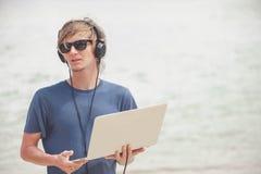 Hübscher blonder Mann, der mit Laptop und Kopfhörern am Strand arbeitet Lizenzfreies Stockfoto