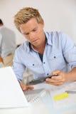 Hübscher blonder Mann, der Mitteilung auf Smartphone schaut Lizenzfreie Stockfotografie