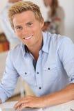 Hübscher blonder Mann, der am Schreibtisch sitzt Lizenzfreies Stockfoto