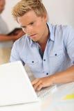 Hübscher blonder Mann, der am Schreibtisch sitzt Lizenzfreie Stockbilder
