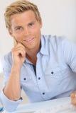 Hübscher blonder Mann, der am Schreibtisch sitzt Stockfotografie