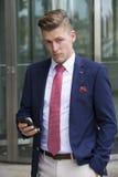 Hübscher blonder Mann in der stehenden Außenseite der Klage mit seinem Telefon Lizenzfreie Stockfotografie