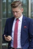 Hübscher blonder Mann in der stehenden Außenseite der Klage mit seinem Telefon Stockbild