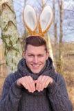 Hübscher blonder Mann im Park mit den Häschenohren Stockbilder