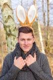Hübscher blonder Mann im Park mit den Häschenohren Stockbild