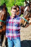 Hübscher blonder Mann mit braunen Pferden Stockfotos