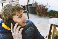 Hübscher blonder Mann, sprechend am Handy und draußen sitzen Stockfotos