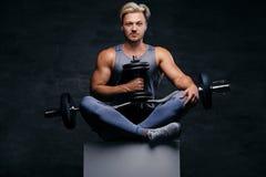 Hübscher blonder sportlicher Mann sitzt auf einem weißen Kasten mit den gekreuzten Beinen und hält Dummkopfsatz Lizenzfreie Stockfotos