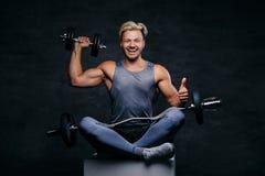 Hübscher blonder sportlicher Mann sitzt auf einem weißen Kasten mit den gekreuzten Beinen und hält Dummkopfsatz Stockfotografie