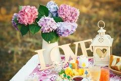 Hübscher Blumenstrauß der Hortensie blüht in einem Weinleseglas Blumendekor auf dem Gartentisch Lizenzfreie Stockbilder