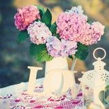 Hübscher Blumenstrauß der Hortensie blüht in einem Weinleseglas Blumendekor auf dem Gartentisch Stockfoto