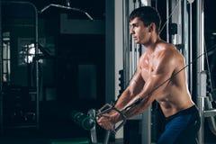 Hübscher Bodybuilder arbeitet Übung in der Turnhalle hochdrücken aus Lizenzfreie Stockfotos