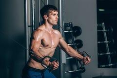 Hübscher Bodybuilder arbeitet Übung in der Turnhalle hochdrücken aus Lizenzfreies Stockbild