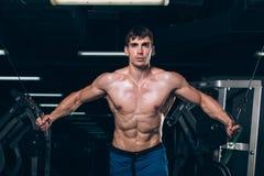 Hübscher Bodybuilder arbeitet Übung in der Turnhalle hochdrücken aus Stockfotos