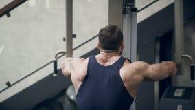 Hübscher Bodybuilder führt eine Übung auf dem Trainer in der Turnhalle durch Junger Sportler hebt seine Hände an stock video