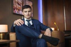 Hübscher Bräutigam, der auf dem Stuhl im Hotel sitzt Stockfotos