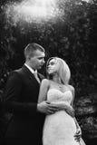 Hübscher Bräutigam, der blonde Braut von hinten im Wald-b&w umarmt Lizenzfreies Stockbild