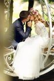 Hübscher Bräutigam, der blonde schöne Braut in magischer Fee t küsst Stockfotografie