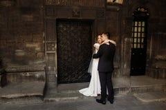 Hübscher Bräutigam, der Braut, Jungvermähltenpaare, blonde Frau und s umarmt Stockfotografie