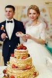 Hübscher Bräutigam der glücklichen Hochzeitspaare und blonde Braut, die Feinkostgeschäft isst Stockfotografie