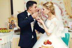 Hübscher Bräutigam der glücklichen Hochzeitspaare und blonde Braut, die Feinkostgeschäft isst Stockbild