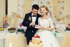 Hübscher Bräutigam der glücklichen Hochzeitspaare und blonde Braut, die Feinkostgeschäft isst Lizenzfreie Stockfotografie