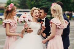Hübscher Bräutigam in der Klage, die elegante blonde Braut mit bridesm umarmt Stockfotos