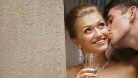 Hübscher Bräutigam küsst die bezaubernde lächelnde Braut mit dem Champagnerglas in der Backe stock video