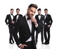 Hübscher Bräutigam mit Bart steht vor dem Gruppendenken Stockbilder